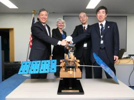 NASA and JAXA leaders shaking hands at the DPR sign-off event.