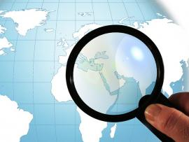 Magnifying glass over a globe.