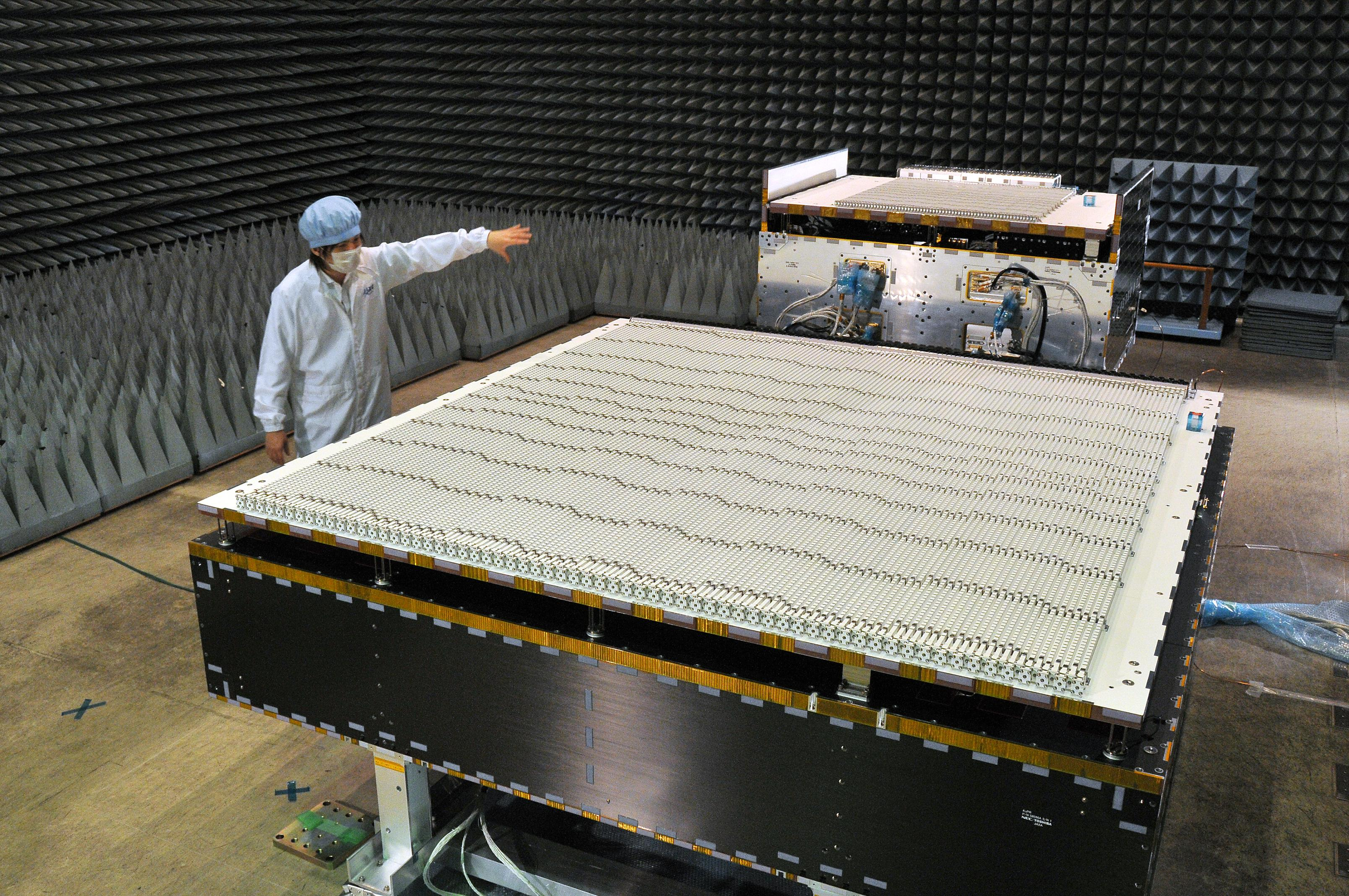 A JAXA scientist standing next to the Dual-frequency Precipitation Radar (DPR) i