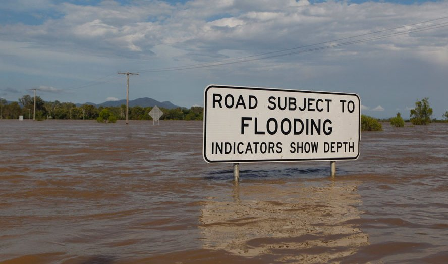 "Flooded road in Australia, submerged sign reading ""Road subject to flooding"""