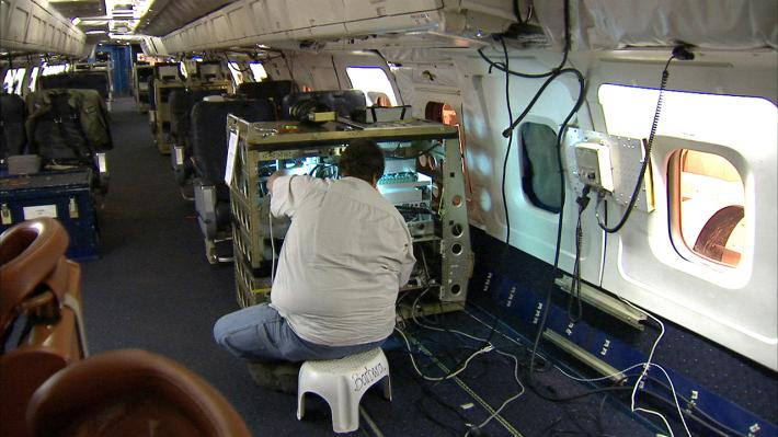 Scientist within the DC-8 preparing instruments