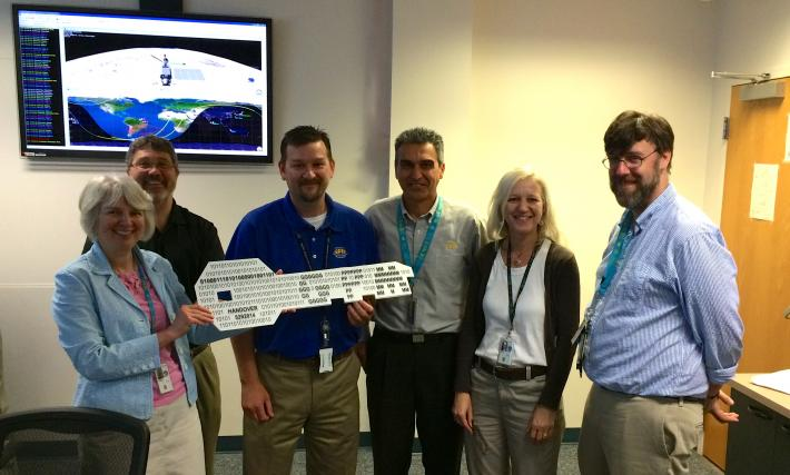 "On May 29, GPM Deputy Project Manager Candace Carlisle (left) handed over the ""key"" to the GPM Core Observatory to GPM Mission Director James Pawloski (center, blue shirt). Also pictured, left to right, Wynn Watson, Art Azarbarzin, Gail Skofronick-Jackson and David Ward."