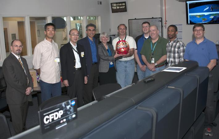 In the Mission Operations Center on May 16, 2014, GPM's NASA and Japan Aerospace Exploration Agency project managers deliver the completed Daruma doll