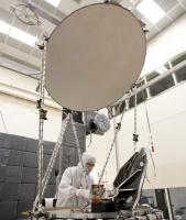 Engineer working on the GMI in a lab, with large reflictive dish in center.
