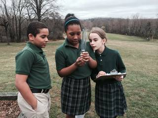 Students reading a rain gauge