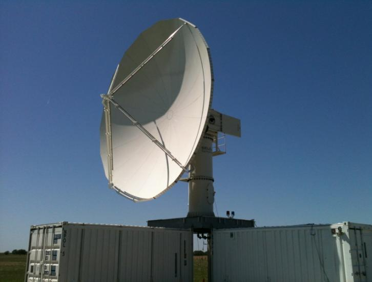 The NPOL instrument, a large radar dish attached to a trailer under a blue sky